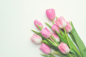 Top view of first spring bouquet of pink tulips on white background with copy space. Beautiful spring background for International Womens day, Mother's day, March 8, Valentines day