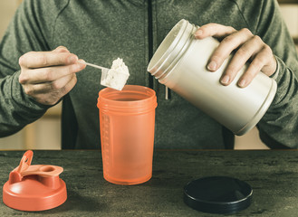 man puts a portion of protein in a shaker, against a background of a dark kitchen table, a top view, a sporty lifestyle