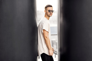 Hipster style guy. Fashion man standing near black wall