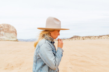 Young woman wearing hat walking on desert