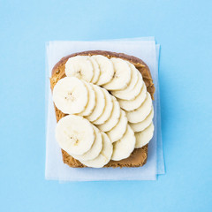 One bread toast smeared with peanut butter on top with banana slices on a blue background. Minimalistic vegan food concept. Top view, flat lay