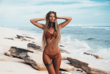 Sexy tattoed girl with tanned skin walking along the beach. Beautiful young blond woman with long hair in a red swimsuit resting by the ocean. A tourist with a beautiful figure on vacation. Close up