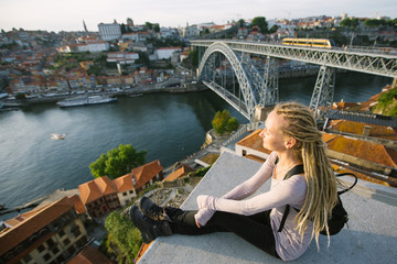 Young woman with blond dreadlocks on view point opposite the Dom Luis I bridge, Porto, Portugal.