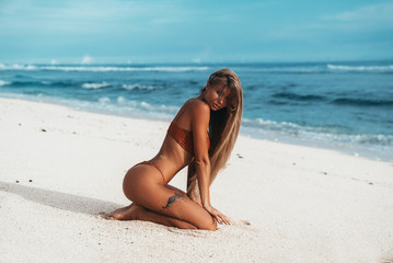 Sexy girl with a tattoo on her leg rests on the beach. Beautiful woman with tanned skin in a red bikini sits on the sand near the ocean