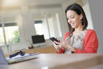 Brunette woman using smartphone in office