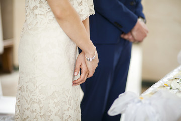 Closeup image of brides hands on marriage ceremony inside church