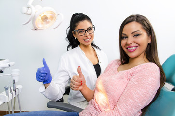 Young woman dentist / nurse and her patient with braces in chair showing thumbs up and smiling