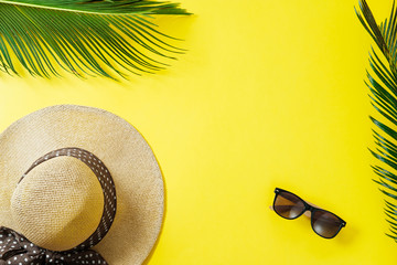 Travel concept: hat, palm leaf and sun glasses on yellow background. Top view, flat lay, space for text