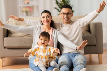 family, parenthood and people concept - happy mother, father with baby daughter at home
