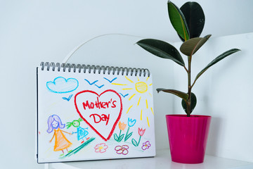 child print. congratulation with happy mother day. plant in pot near child picture