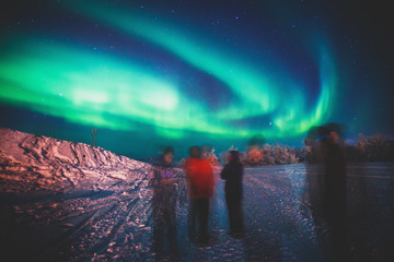 Beautiful picture of massive multicolored green vibrant Aurora Borealis, also known as Northern Lights in the night sky over winter Lapland landscape, Norway, Scandinavia