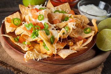 Corn Mexican nachos with beef, jalapeno, cheese, pepper, olives and chili con carne on a wooden background. Lime, Ketchup, sour cream and mayonnaise souce seasoning.