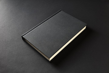 Blank book cover on black paper background.