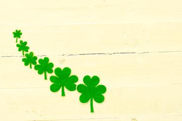 Green shamrocks on a wooden background.