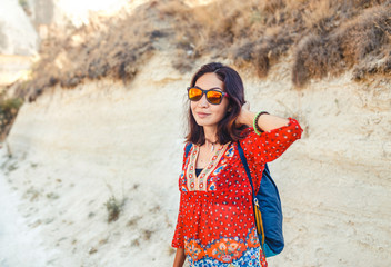 Young happy woman traveler alone hiking with backpack in valley of Cappadocia, Turkey