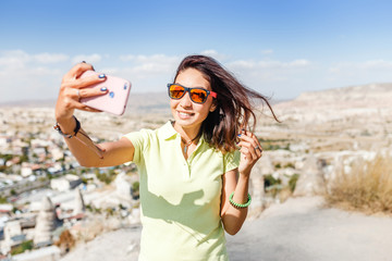 smiling woman in sunglasses taking selfie photo on a smartphone in Cappadocia, Turkey
