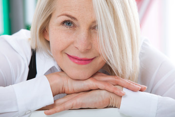 Lovely middle-aged blond woman with a beaming smile sitting at office looking at the camera