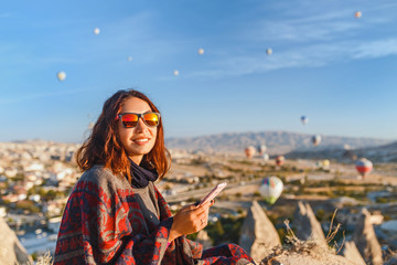 A tourist girl talks by the phone of the hills in Cappadocia in Turkey. Travel, tourism, hiking, vacation.