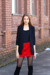 Street fashion, urban style. Girl in jacket, t-shirt, short skirt and high boots