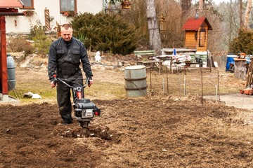 Farmer working in the field. Spring work on the farm. Man plowing the garden.