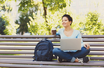 Smiling woman with laptop outdoors