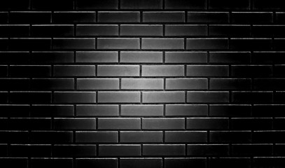 black brick wall with a light center for designers background texture