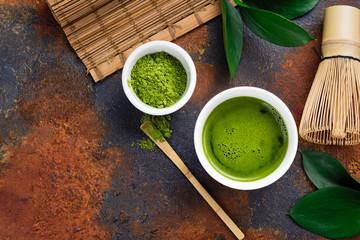 Green matcha tea drink and tea accessories on dark rusty background
