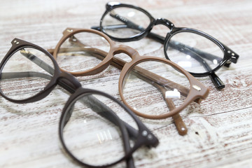 Three pairs of fashionable men's eyeglass frames on white wooden background