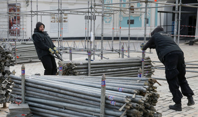 Workers replace pipes as they work on the construction of a stage in central Kiev