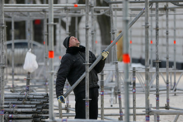 A worker holds a pipe as he works on the construction of a stage in central Kiev