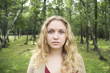 Close-up portrait of beautiful young woman with blond hair in forest