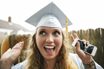 Close-up of happy female graduate holding smart phone