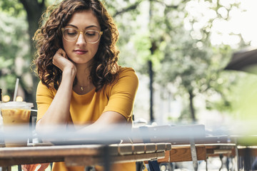 Young woman with eyeglasses having coffee while sitting at table in cafe