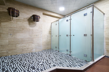 Three empty public showers with wooden ice bucket for health, sauna showers interior