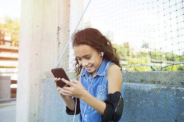 Smiling girl with elbow pads and headphones listening music through smart phone in city
