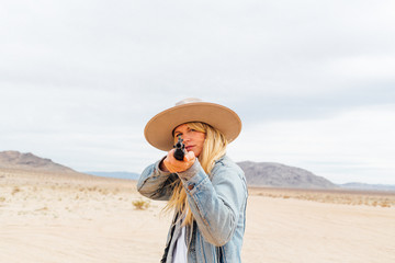 Portrait of young woman wearing hat aiming gun on desert at Joshua Tree National Park