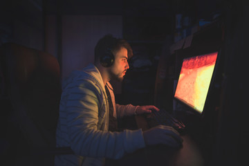 A cute male gamer sits in a cozy room behind a computer and plays games. Gamer plays horror game at night. Computer games. Gamer concept.