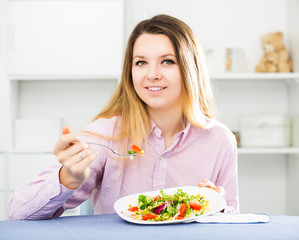 Woman tasting fresh green salad