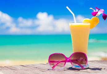 picture of fresh banana and pineapple juice and sunglasses on tropical beach