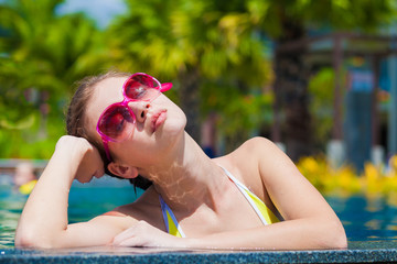 Beautiful young woman in sunglasses relaxing in luxury pool