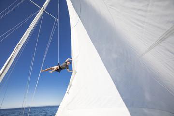 Man climbing the mast of a sailboat