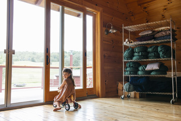 Smiling girl riding tricycle indoors in loft