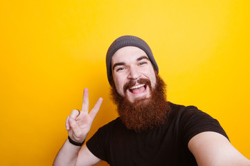 Happy bearded man showing two fingers and making selfie over yellow background