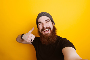 Cheerful smiling bearded hipster man showing thumbs up and making selfie over yellow background