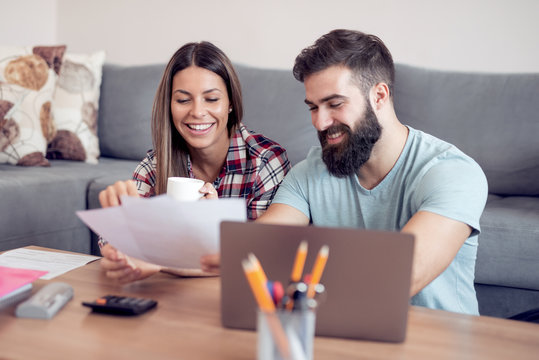 Young couple calculating bills at home