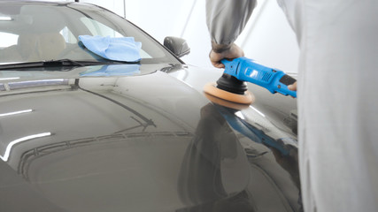 A man in a special suit polishes a gray car body, a tool for polishing cars, into a workshop.