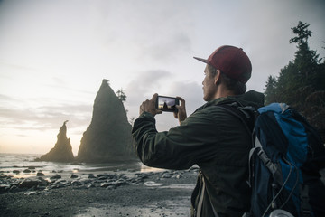 Young hiker taking picture of ocean from smartphone