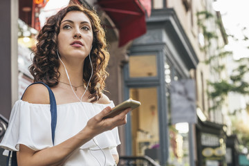 Thoughtful woman looking away and listening music through smart phone while standing in city
