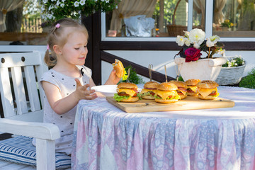 3 year old girl eats a lot of burgers at the table outdoor