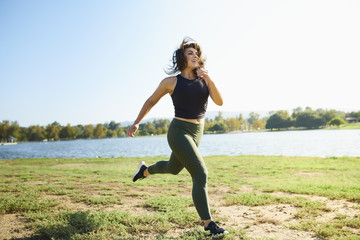 Smiling young woman jogging near lake on sunny day